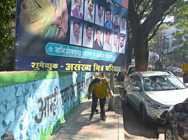 Pedestrians bend down to walk on a footpath as an illegal hoarding encroached the footpath on Dhole Patil road.(Shankar Narayan/HT PHOTO)