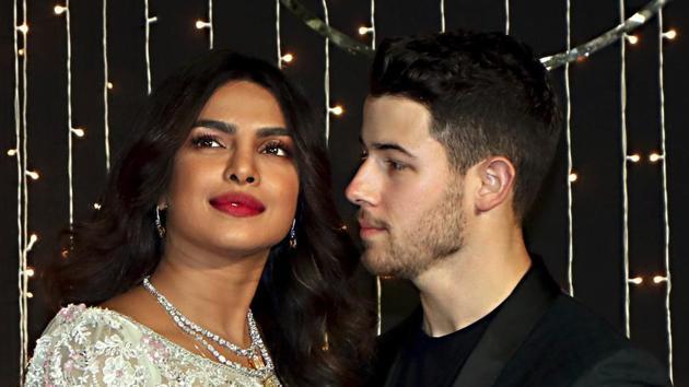 Bollywood actor Priyanka Chopra with husband-singer Nick Jonas pose for photos during their wedding reception, in Mumbai.(PTI)