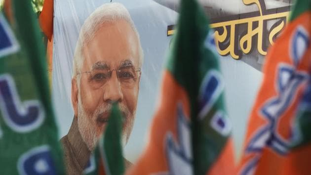 Bharatiya Janata Party (BJP) workers carry flags past a poster of Prime Minister Narendra Modi during an event to celebrate the reservation bill passed in the Parliament, in Mumbai on January 10.(AFP File Photo)