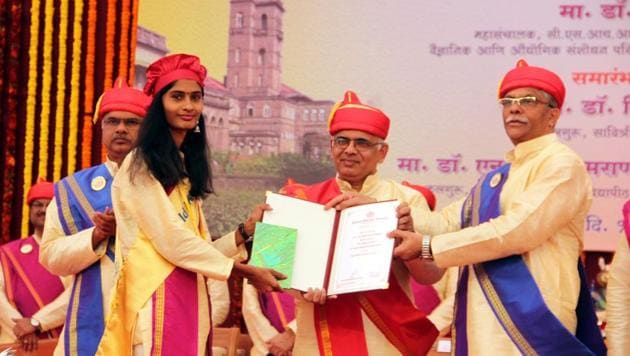 Nitin Karmalkar, vice-chancellor, Savitribai Phule Pune University (right) presented a certificate to a students (left) at the 114th convocation programme on Friday.(HT PHOTO)