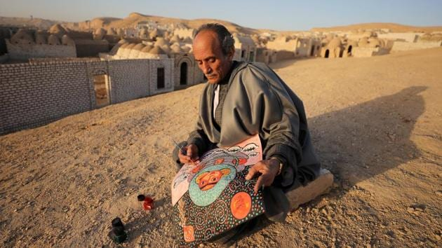 <p>Egyptian artist Hassan el-Shark paints a piece of art with his own handcrafted colours near the &lsquo;City of the Dead&rsquo; in Minya Governorate, Upper...