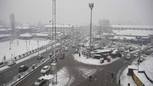 <p>A view of Lal Chowk during snowfall in Srinagar on Wednesday. Flight operations at the Srinagar international airport were halted on Wednesday following poor...