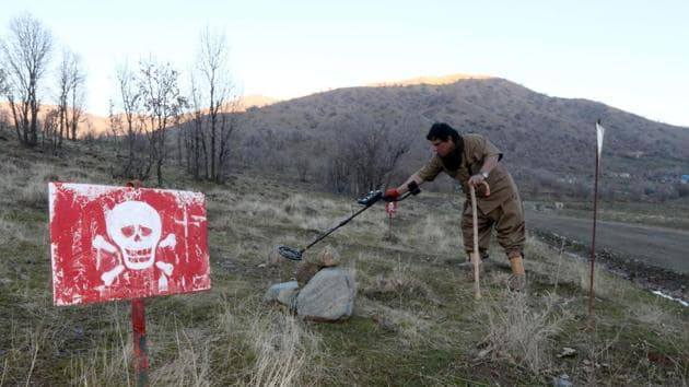 <p>Hoshyar Ali, who lost both legs in landmine explosions, walks in a minefield trying to deactivate the devices on the outskirts of the Kurdish town of...