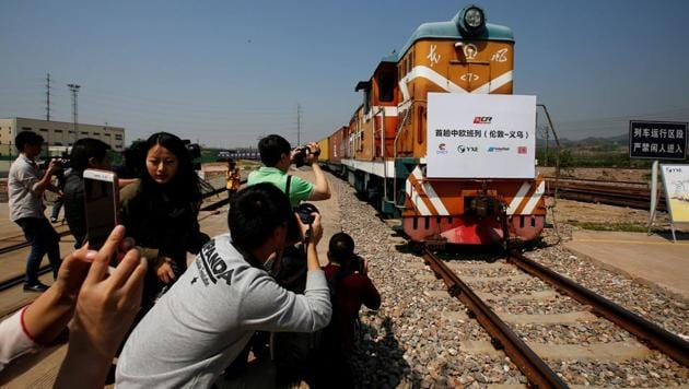 People take pictures as a train carrying containers from London arrives at the freight railway station in Yiwu, Zhejiang province, China, April 29, 2017.(Reuters)