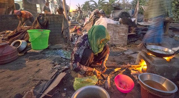 A Rohingya Muslim woman cooks in a semi-dismantled house at a refugee camp in New Delhi in 2015. The UN refugee agency has said it has detected Rohingyas from India are moving to Bangladesh as authorities crack down on them (File Photo)(HT)