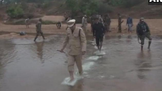 Police and District Administration officials of a village in Bastar waded through water to hoist the Tricolour on the banks of river Indravati.(ANI Photo/Twitter)