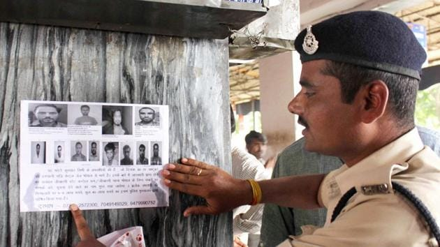 A file photo of a security personnel pasting posters at a railway station of eight SIMI members who had escaped from Central Jail killing a security guard in Bhopal in 2016.(PTI file photo)