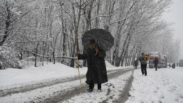 A man walks snow covered Srinagar-Jammu National Highway during fresh snowfall in Qazigund, south Kashmir on January 31.(ANI Photo)