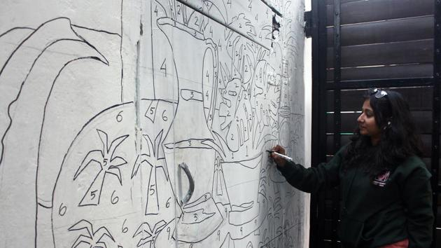 An artist works on a paint by numbers mural outside Studio Khirki which hosted the Irragulars Art Fair(SHivam Saxena-HT)