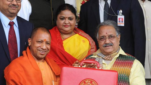 Uttar Pradesh Chief Minister Yogi Adityanath along with state's Finance Minister Rajesh Agarwal displaying budget briefcase ahead of state budget in Vidhan Sabha in Lucknow on Thursday.(ANI)