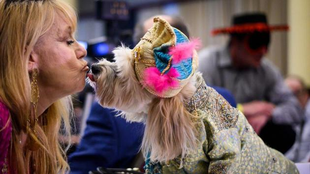 An owner kisses her dog. The annual catwalk also kicks off New York fashion week and the Westminster Kennel Club dog show. (Johannes Eisele / AFP)
