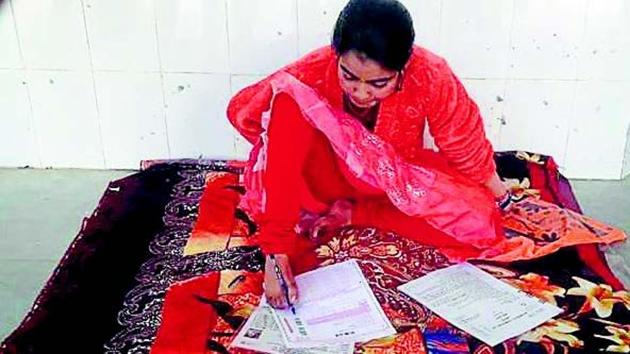 Ankita writes her intermediate exam papers using toes at Chapra Zila High School in Saran district.(HT photo)