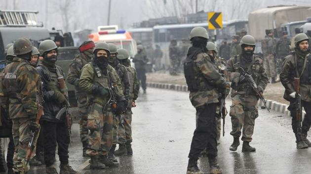 Secuirty forces near the damaged vehicles at Lethpora on the Jammu-Srinagar highway.(HT Photo/ Waseem Andrabi)
