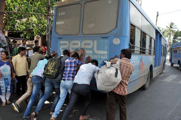 Passengers push a PMPML bus that brokedown at Alka Talkies chowk.(HT/PHOTO)