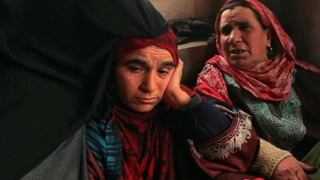Fahmeeda (Left), mother of Adil Ahmad Dar, who claimed responsibility for the Pulwama terror attack, sits inside her home in Gundbagh village in south Kashmir's Pulwama district.(Reuters)