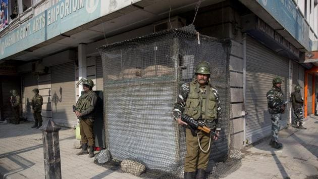 Soldiers stand guard outside a closed market area during a shutdown in Srinagar on Saturday.(AP)