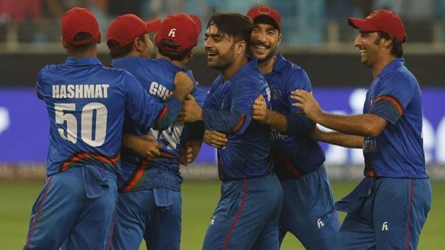 Rashid Khan (3R), captain Asghar Afghan (R) celebrates with teammates.(AFP)