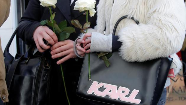People hold white roses as they stand outside the Chanel fashion boutique after news that German haute-couture designer Karl Lagerfeld, artistic director at Chanel and an icon of the global fashion industry for over half a century, has died, aged 85, in Paris, France, February 19, 2019.(REUTERS/Charles Platiau)
