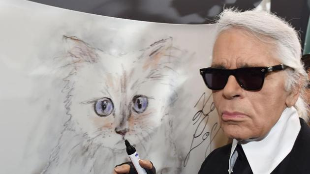 Karl Lagerfeld poses next to a painting of his cat Choupette during the inauguration of the show Corsa Karl and Choupette at the Palazzo Italia in Berlin.(AFP)