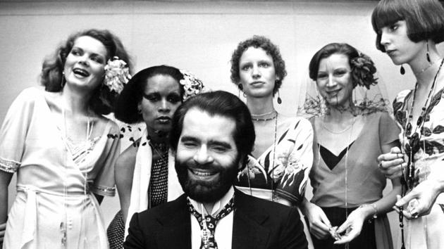 FILE -- In this Nov. 29, 1973 photo German fashion designer Karl Lagerfeld, left, poses with models in Krefeld, Germany. Chanel's iconic couturier, Karl Lagerfeld, whose accomplished designs as well as trademark white ponytail, high starched collars and dark enigmatic glasses dominated high fashion for the last 50 years, has died. He was 85 years old.(Willi Bertram/dpa via AP, file)