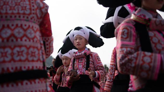 <p>Girls from the Long Horn Miao, a branch of the Miao ethnic minority group, prepare to take part in the annual flower festival or 'Tiaohuajie' in the village...