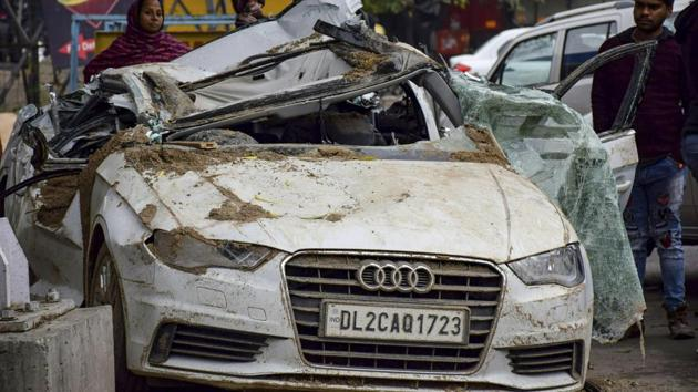 Passers-by look at the mangled remains of an Audi car which collided with a dumper at Rohini, in New Delhi, Wednesday, Feb. 20, 2019, killing three of the four occupants of the car.(PTI)