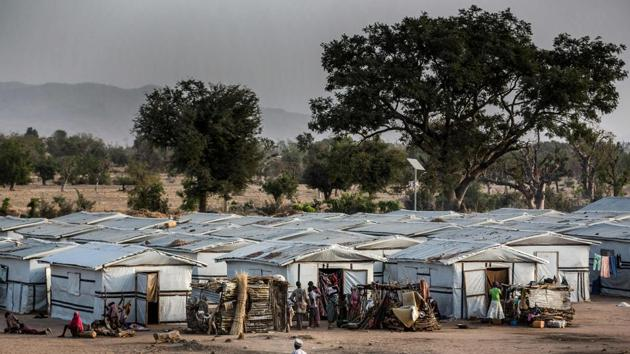 <p>A man rides a bicycle inside a refugee camp in Jimeta, Adamawa State, Nigeria, ahead of the country's general elections set for February 23 after a...