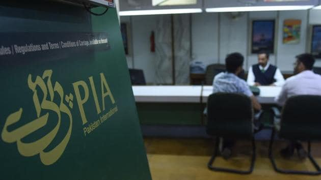 Staff of Pakistan International Airlines (PIA) talk with passengers at a PIA office in Karachi on February 27.(AFP Photo)