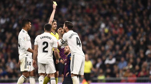 Spanish referee Undiano Mallenco hands a yellow card to Real Madrid's Spanish defender Sergio Ramos during the Spanish league match between Real Madrid CF and FC Barcelona.(AFP)