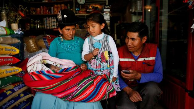 Ana Huanca, her six-week-old baby Luciana, her elder daughter Anabel, 5, and husband Luis, at their food shop in La Paz, Bolivia. In Bolivia, mothers are entitled to 15 days of maternity leave before they give birth and 45 days after they've given birth. However Ana and Luis are among the majority of Bolivian workers who have no regular jobs which would entitle them to benefits like maternity leave. (David Mercado / REUTERS)
