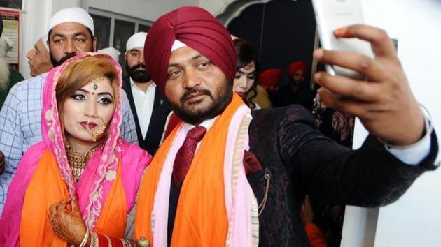 Groom Parvinder Singh taking selfie with his wife (Pakistan national) Kiran Sarjeet Kaur after their marriage ceremony at Gurdwara Khel Sahib in Patiala on Saturday.(HT Photo)
