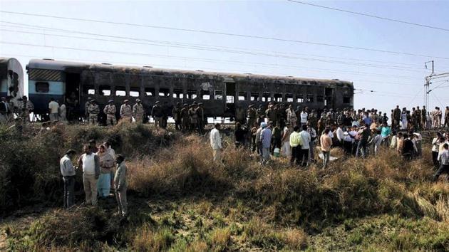 People gathered near the bogies of Samjhuata Express burn after an explosion in Delhi-Atari Samjhauta Express at Dewana village near Panipat on February 19, 2007.(PTI Photo)