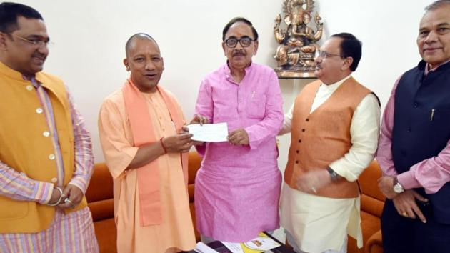 Yogi Adityanath handing over cheque of Rs 2.51 lakh to UP BJP chief Mahendra Nath Pandey in Lucknow on Monday.(HT)