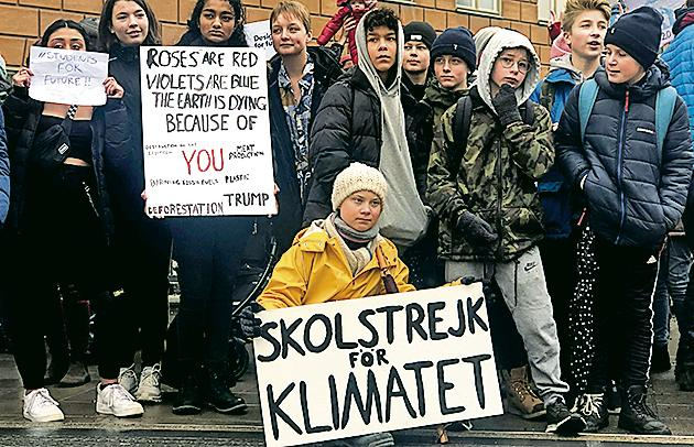 Greta Thunberg (yellow jacket) at a protest next to Sweden's Parliament in Stockholm on March 8, 2019.(Reuters)