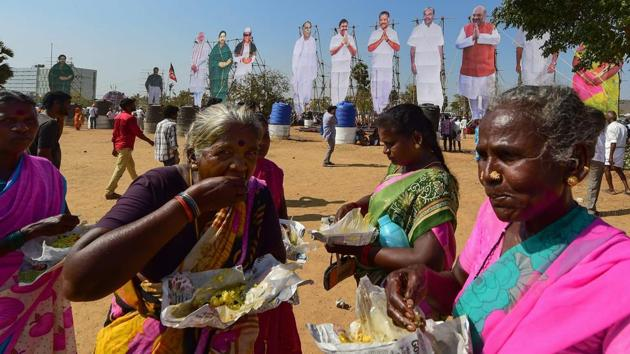 Supporters have their meals in the backdrop of huge cut-outs of political leaders at a rally of the BJP-AIADMK-PMK alliance, in Chennai on March 6.(PTI)