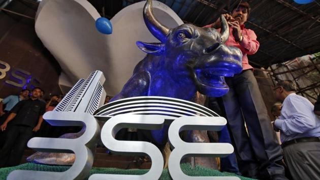 A man ties a balloon to the horns of a bull statue at the entrance of the Bombay Stock Exchange (BSE).(REUTERS)
