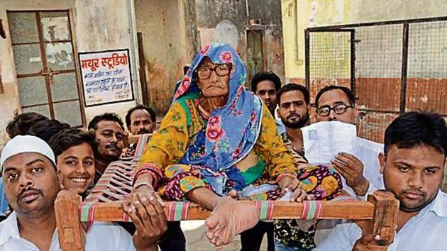 Family members and volunteers carry an elderly voter to a voting centre in Kota during the last assembly election in Rajasthan.(HT File)