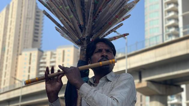 Flute player Raju too lures rats - mallrats in his case. He plays his pipe all day long outside the glass-walled South Point Mall in Gurugram.