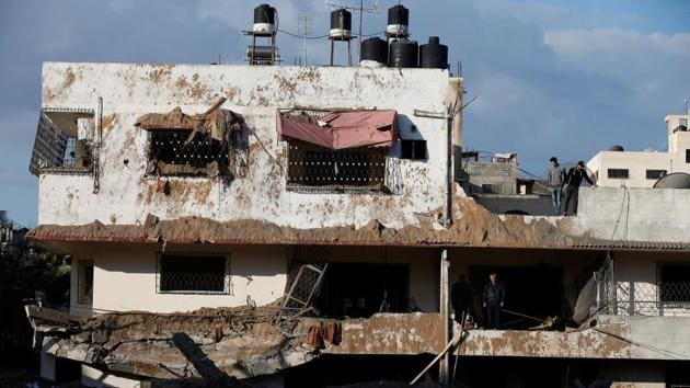 Palestinians inspect their house that was damaged in a nearby Israeli air strike in Gaza City on March 26.(REUTERS)