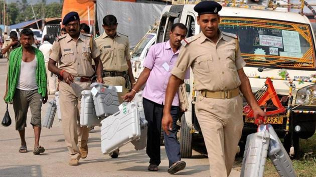Police personnel carry EVM machines to polling booths.(PTI)