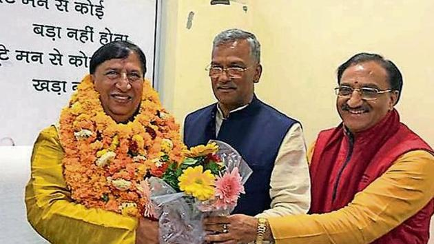 Chief minister Trivendra Singh Rawat (centre) welcomes the acting president of BJP state unit, Naresh Bansal (L), at party state headquarters in Dehradun on Wednesday, March 27, 2019.(Vinay Santosh Kumar / HT Photo)