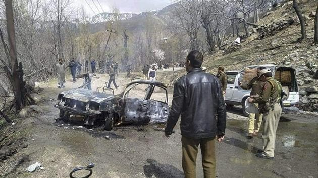 Security personnel inspect the mangled remains of a car which exploded near a CRPF convoy on the Jammu-Srinagar highway at Banihal in Ramban district of Jammu and Kashmir on March 30.(PTI)