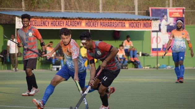 Excellency Academy (orange) in action against Food Corporation India, Pune, during the finals of the first edition Moti John memorial hockey tournament at Dhyan Chand hockey stadium on Sunday.(HT/PHOTO)