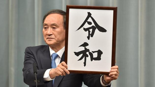 "Japan's Chief Cabinet Secretary Yoshihide Suga holds the new era name ""Reiwa"" during a press conference at the prime minister's office in Tokyo.(AFP)"