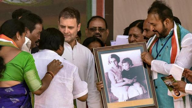 Congress party workers present a framed portrait of Indira Gandhi to Congress President Rahul Gandhi during a public rally at Zaheerabad,Telangana, on Monday.(PTI)