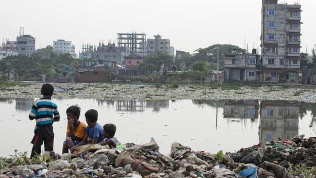 Bangladeshi children sit on garbage piled up by the river Buriganga in Hazaribagh area in Dhaka, Bangladesh.(AP Photo)