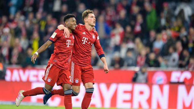 Bayern Munich's Austrian defender David Alaba and Bayern Munich's German midfielder Leon Goretzka celebrate after the German first division Bundesliga football match between FC Bayern Munich and BVB Borussia Dortmund(AFP)