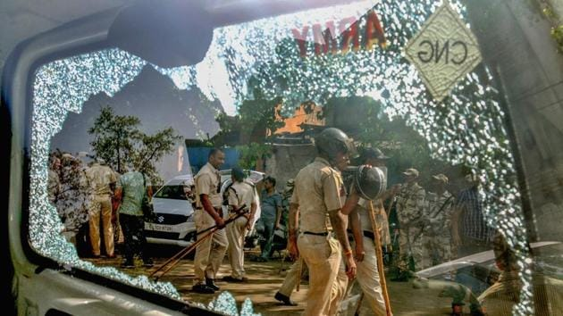 New Delhi: Police personnel are seen through a broken car window following clashes between locals and the police during a sealing drive in Mayapuri, New Delhi, Saturday, April 13, 2019. (PTI Photo) (PTI4_13_2019_000145B)(PTI)