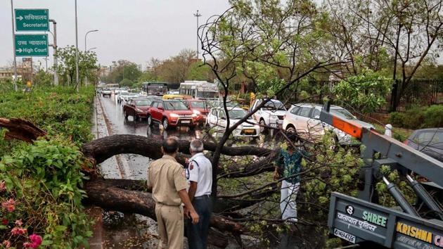 Jaipur: Police personnel look on as people remove a fallen tree obstructing traffic, after a thunderstorm, in Jaipur, Tuesday, April 16, 2019.(PTI)