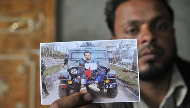 Farooq Dar, who was used as a human shield by army, sits in his home in Chill village in Budgam district and holds a picture of him being tied on a jeep.(HT file photo)